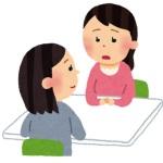 机を挟んで向かい合って座っている二人の女性