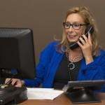 電話で話をしながら、PCを操作している女性