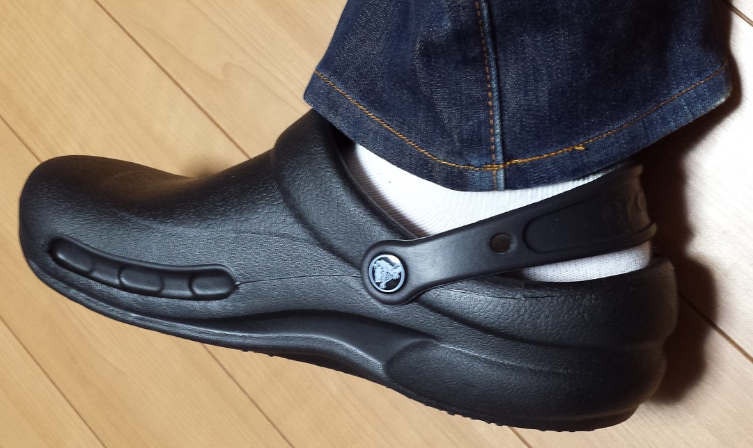 crocs bistro (クロックス ビストロ)と青いジーンズを履いており、脱げ防止用のストラップを装着した状態を真横から見た様子