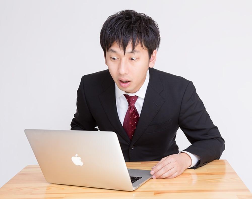 PCの画面を見て驚いているサラリーマン風の若い男性