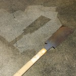 のこぎりでコンクリートを保護し、その周囲に高圧洗浄機による掃除を行い、その後のこぎりをどかした状態