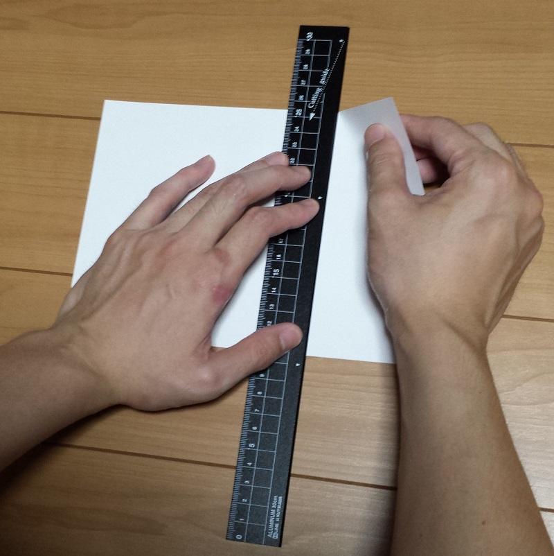 正面から見た定規で紙を切っている様子