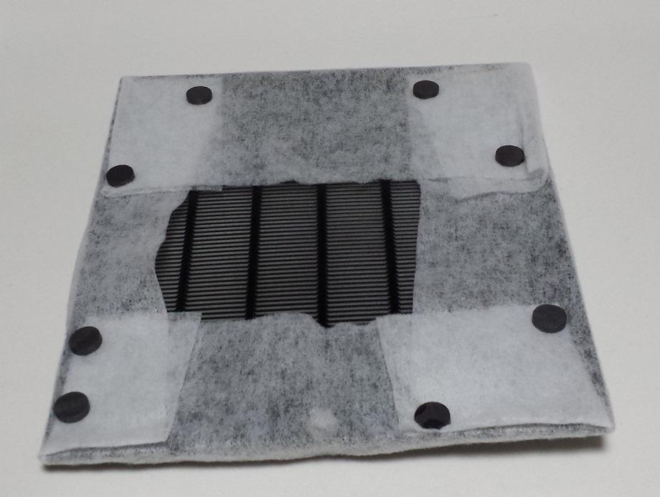 レンジフードフィルターの背面に8個の磁石を貼り付けて固定している様子