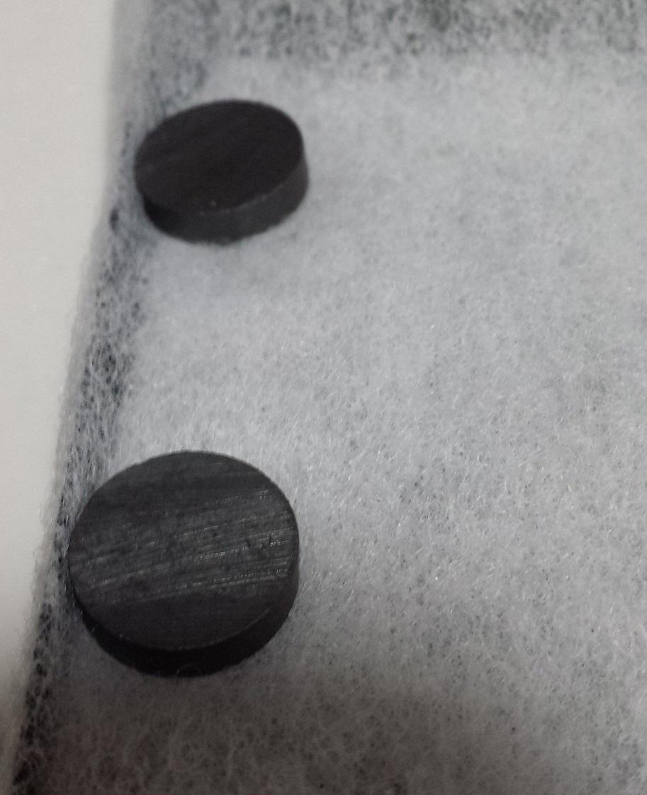 レンジフードフィルターの背面に磁石を貼り付けて固定している様子