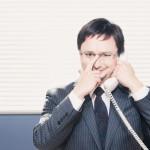 電話で話しながらメガネを持ち上げているサラリーマン風の男性
