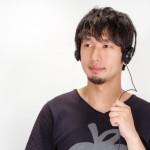 ヘッドホンで音楽を聴いているヒゲを生やしている男性