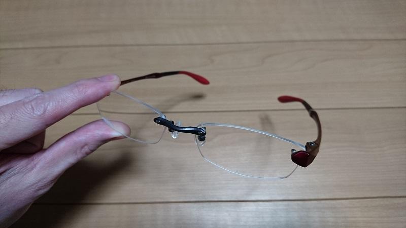 左手で持っている赤いフレームのふち無しのメガネ