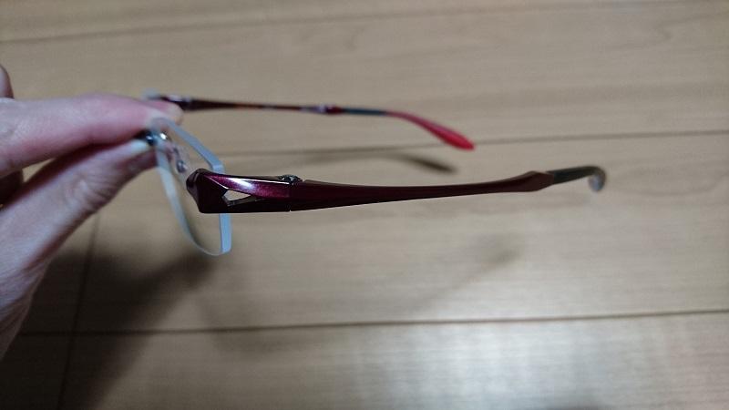 左手で持っている赤いフレームのふち無しのメガネを側面から見た様子