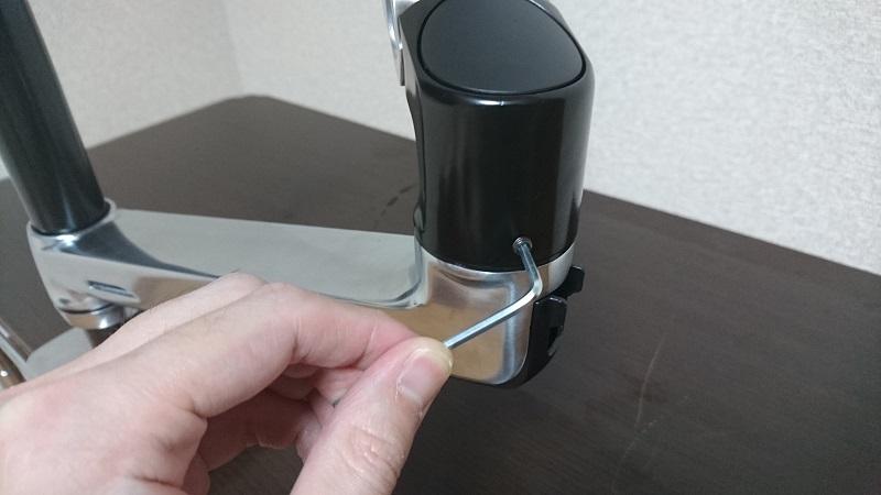 エルゴトロン 45-248-026(デュアル スタッキング)モニターアームの上部パーツのイモネジを調整している様子