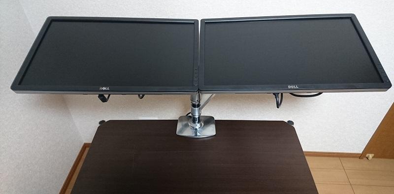 エルゴトロン 45-248-026(デュアル スタッキング)モニターアームを使って、2台のモニターを横に並べて上に向けて設置している様子
