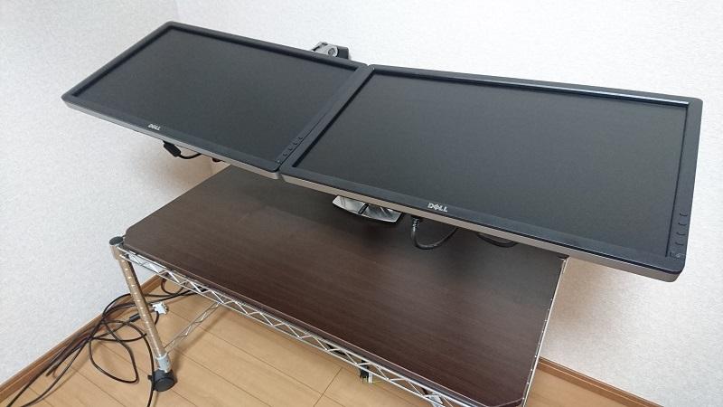 エルゴトロン 45-248-026(デュアル スタッキング)モニターアームを使って、2台のモニターを横に並べて上に向けて設置している様子を斜め上から撮影した画像