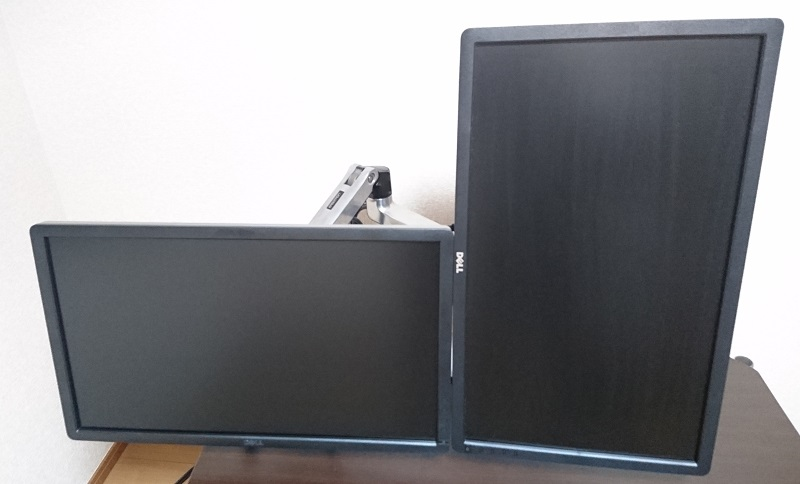 エルゴトロン 45-248-026(デュアル スタッキング)モニターアームを使って、2台のモニターを横長と縦長の状態で横に並べて設置している様子