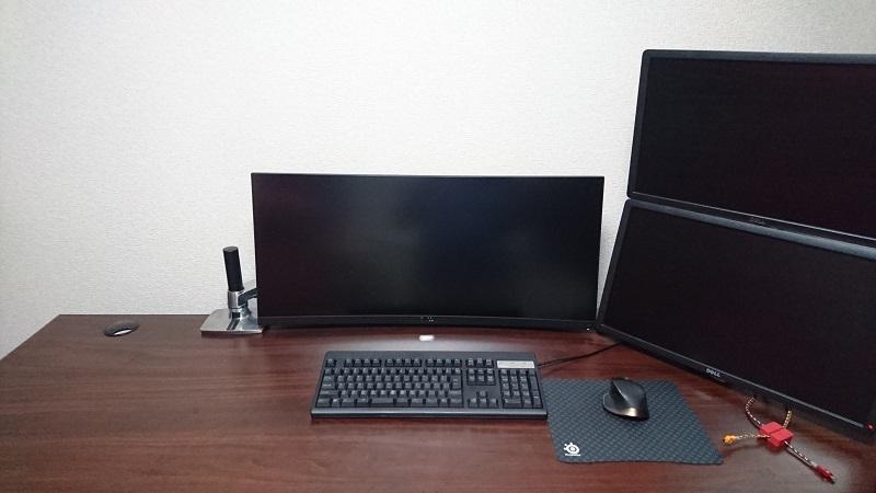 机にエルゴトロン LX モニターアームを使用して、複数のモニターを設置している様子