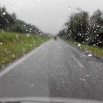水滴が付いている走行中の車のフロントガラス