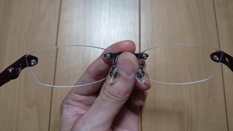 左手で眼鏡のレンズ間のフレーム部を持っている様子