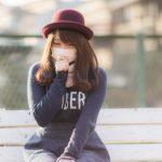 右手で咳を抑え、マスクをしている赤い帽子をかぶった若い女性
