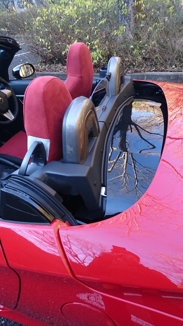 横から見たオープンカー状態の赤いコペン(LA400K)のシート後方の様子