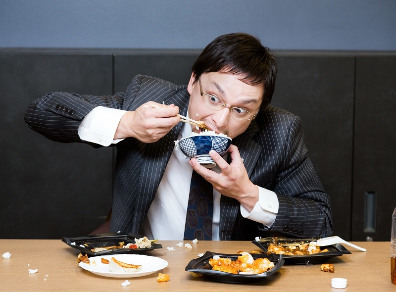 眼鏡をかけているサラリーマン風の男性が、ご飯をこぼしながら食べている様子