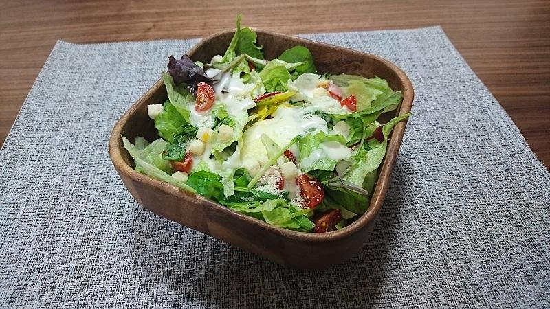 テーブルの上に置いてある木製の容器に盛られたシーザーサラダ