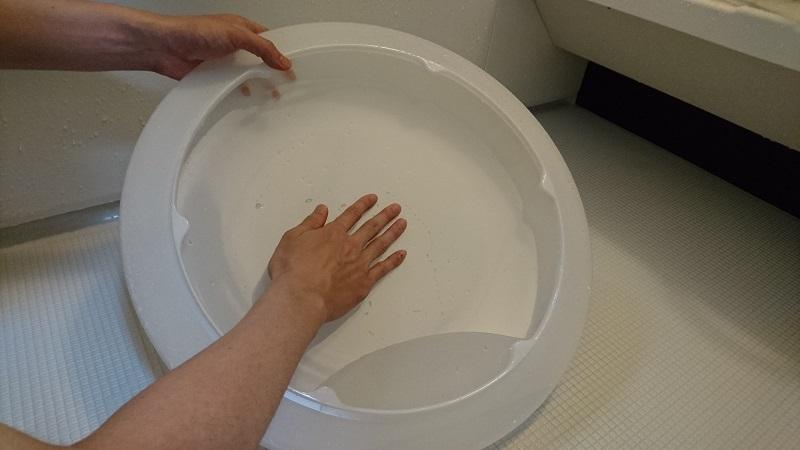 シーリングライトのカバーの内側を、シャワーでぬるま湯をかけながら手の指の腹でこすり洗いしている様子