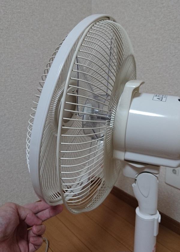ロック機構を解除し、扇風機のファン前面カバーの下部を手前(扇風機の前面側)に引っ張っている様子