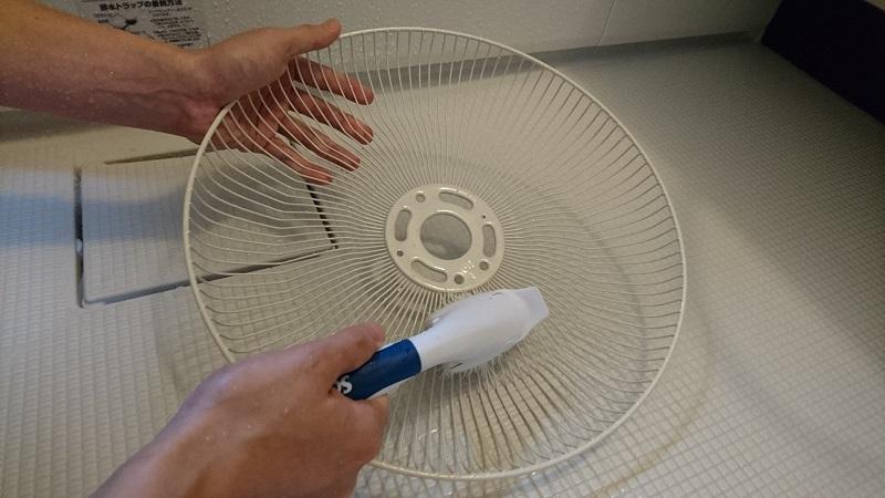 ファン後面カバーを、食器用中性洗剤を付けたブラシでこすり洗いしている様子