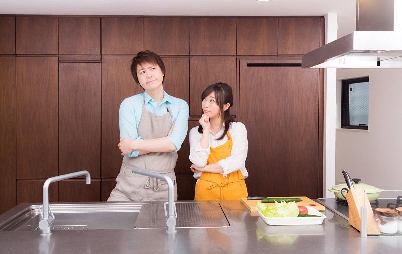 キッチンで考え込んでいるエプロンを付けた若い男女
