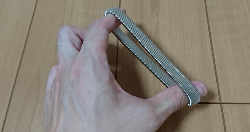 ダイソーのスプリングアームバンドに指で力を加え、広げている様子