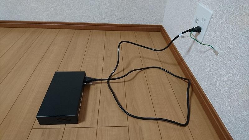 コンセントに電源ケーブルが接続されている状態のヤマハ L2スイッチ SWX2200-8G