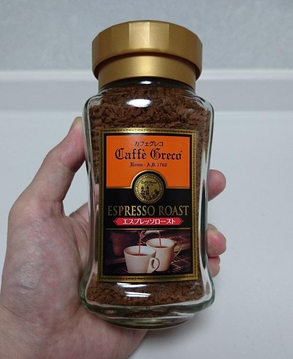 エスプレッソのインスタントコーヒー、UCC カフェグレコ エスプレッソローストの瓶を左手で持っている様子