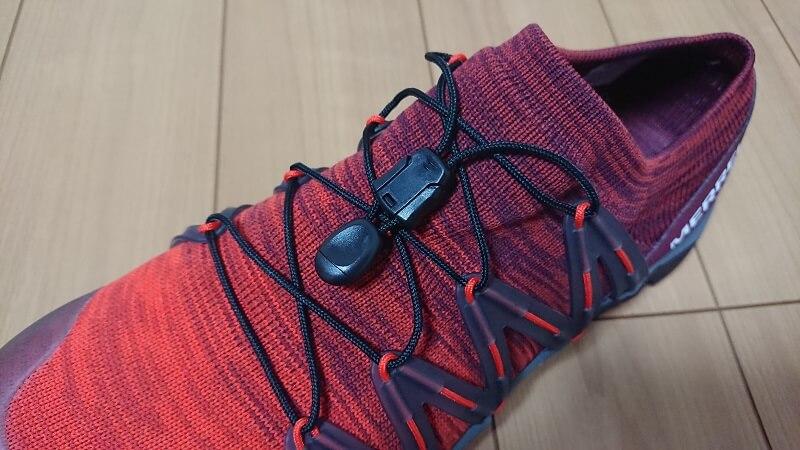 ベア アクセス フレックス ニットの足の甲にある留め金を、靴紐の部分にしまっている様子