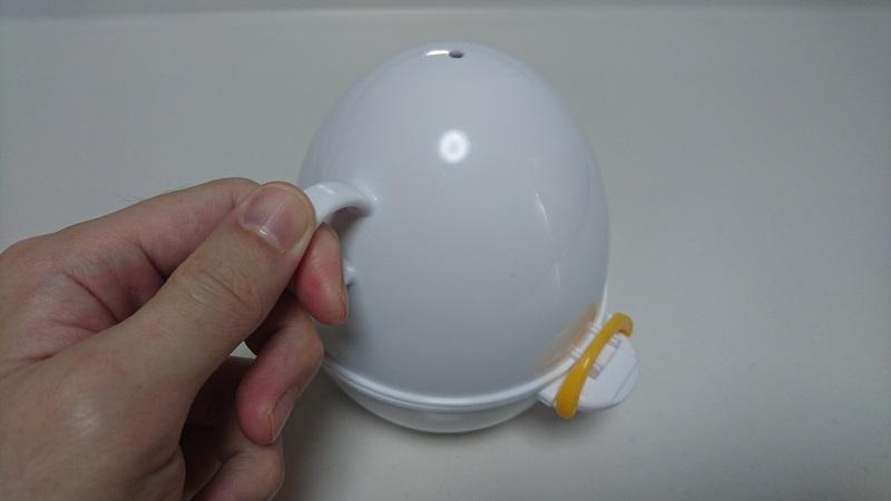 レンジでらくチンゆでたまごの上側容器にある取っ手を持っている様子