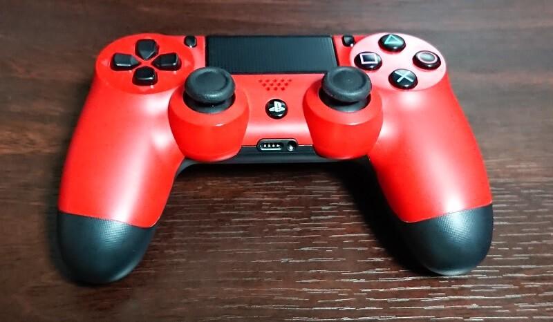 机の上に置かれているPlayStation4の赤いコントローラー DUALSHOCK 4