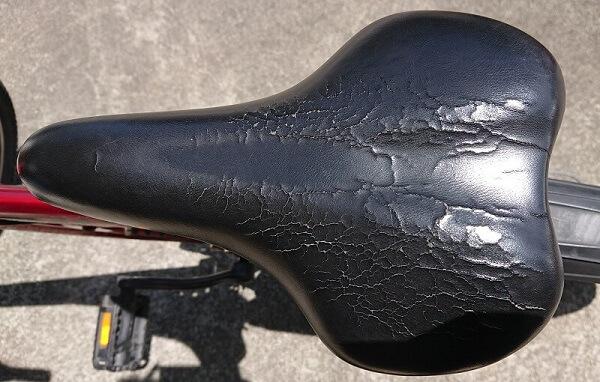 表面がひび割れし、穴が空いている自転車のサドル