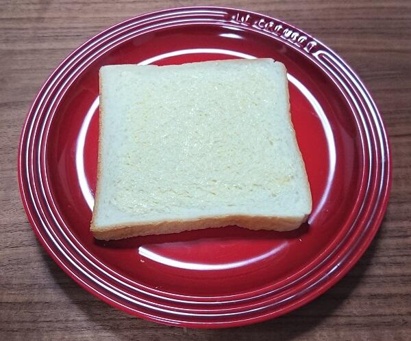 赤い皿の上に置いてあるバターを塗った食パン
