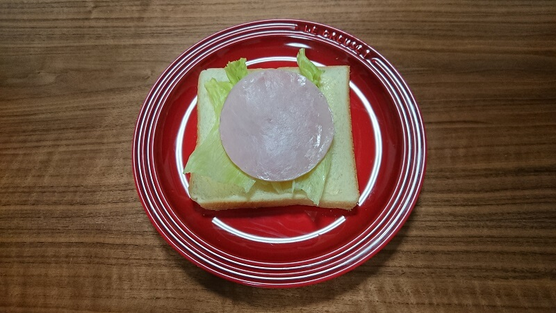 食パンの上に、レタスとハムが置いてある様子