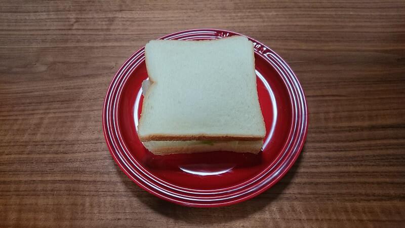 レタスとハム、チーズをはさんだパンが、赤い皿の上に置いてある様子