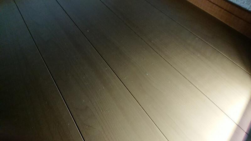 掃除機のLEDライトに照らされて、ゴミが見える床の様子